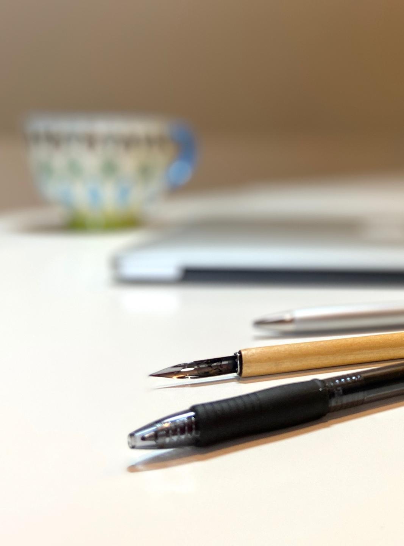 Writing tools, macbook pro, pier one mug, writing pens