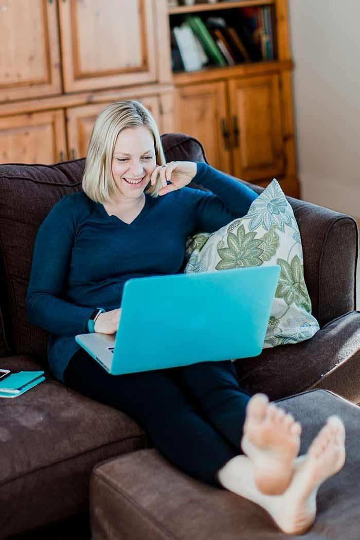 Picture of Stacey Nachajski sitting on couch with teal laptop in her lap
