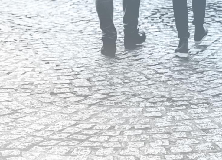 Two peoples feet walking down the street