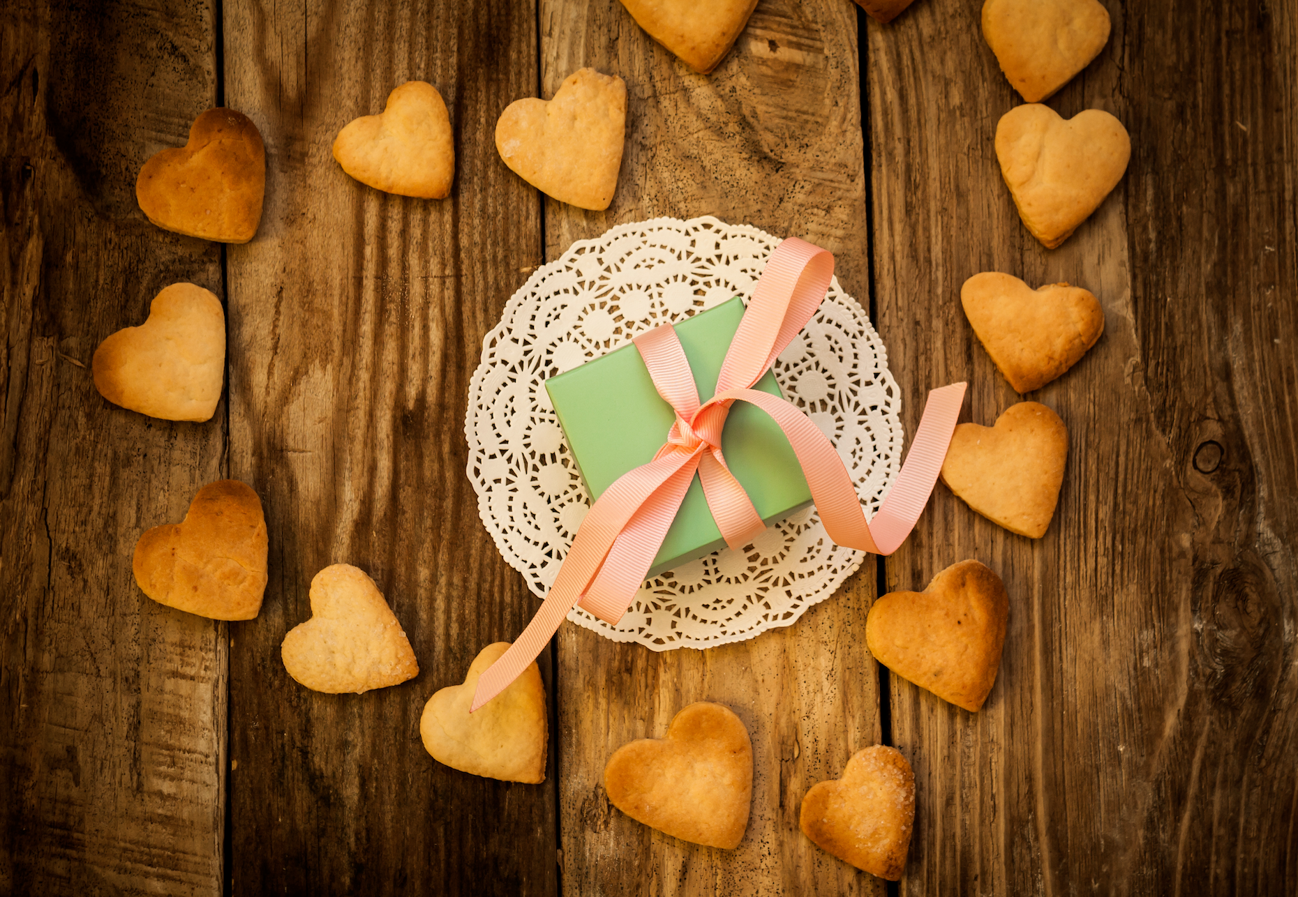 heart-shaped cookies and blue gift with pink ribbon on doiley