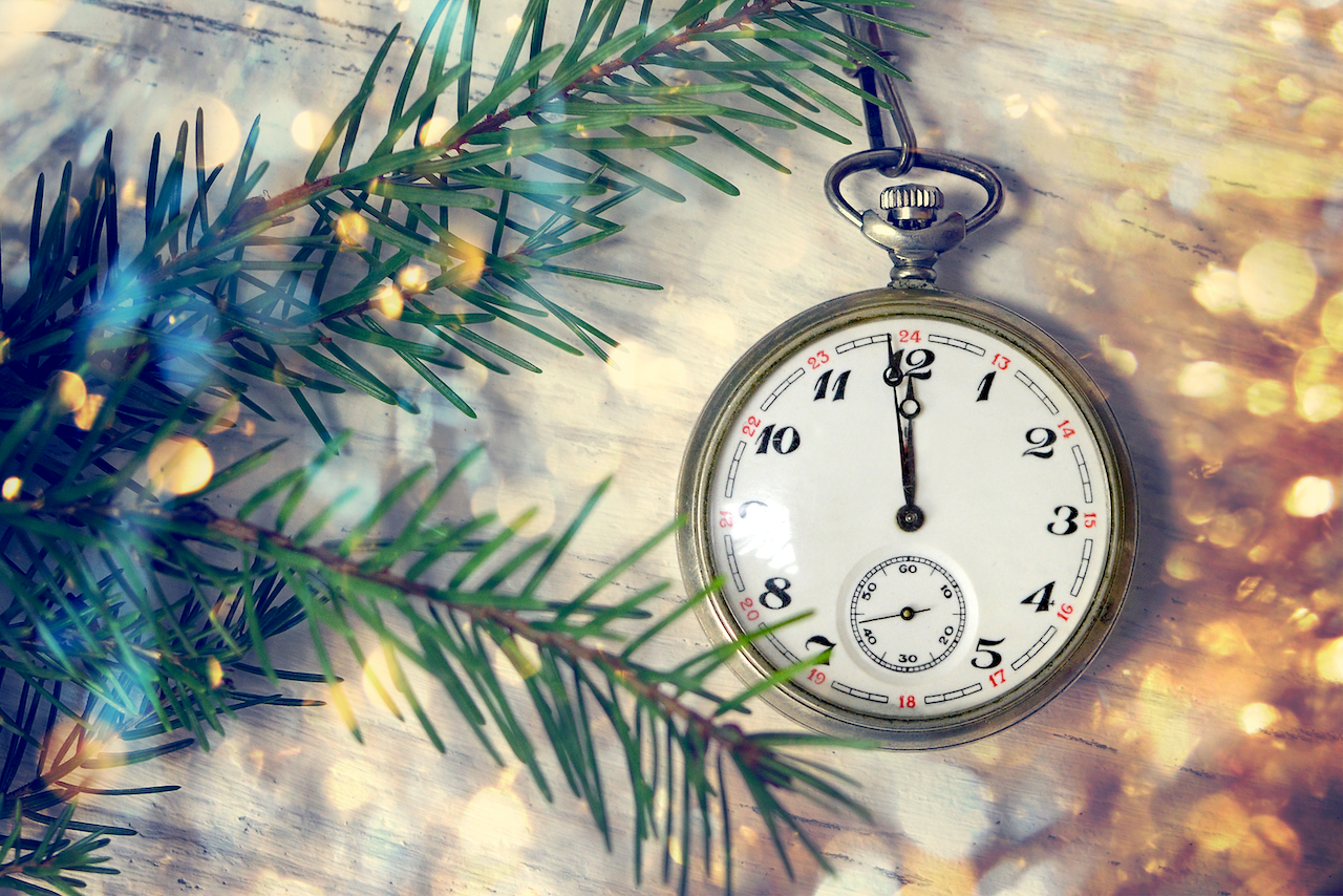 pocket watch with pine tree branch and bokeh lights