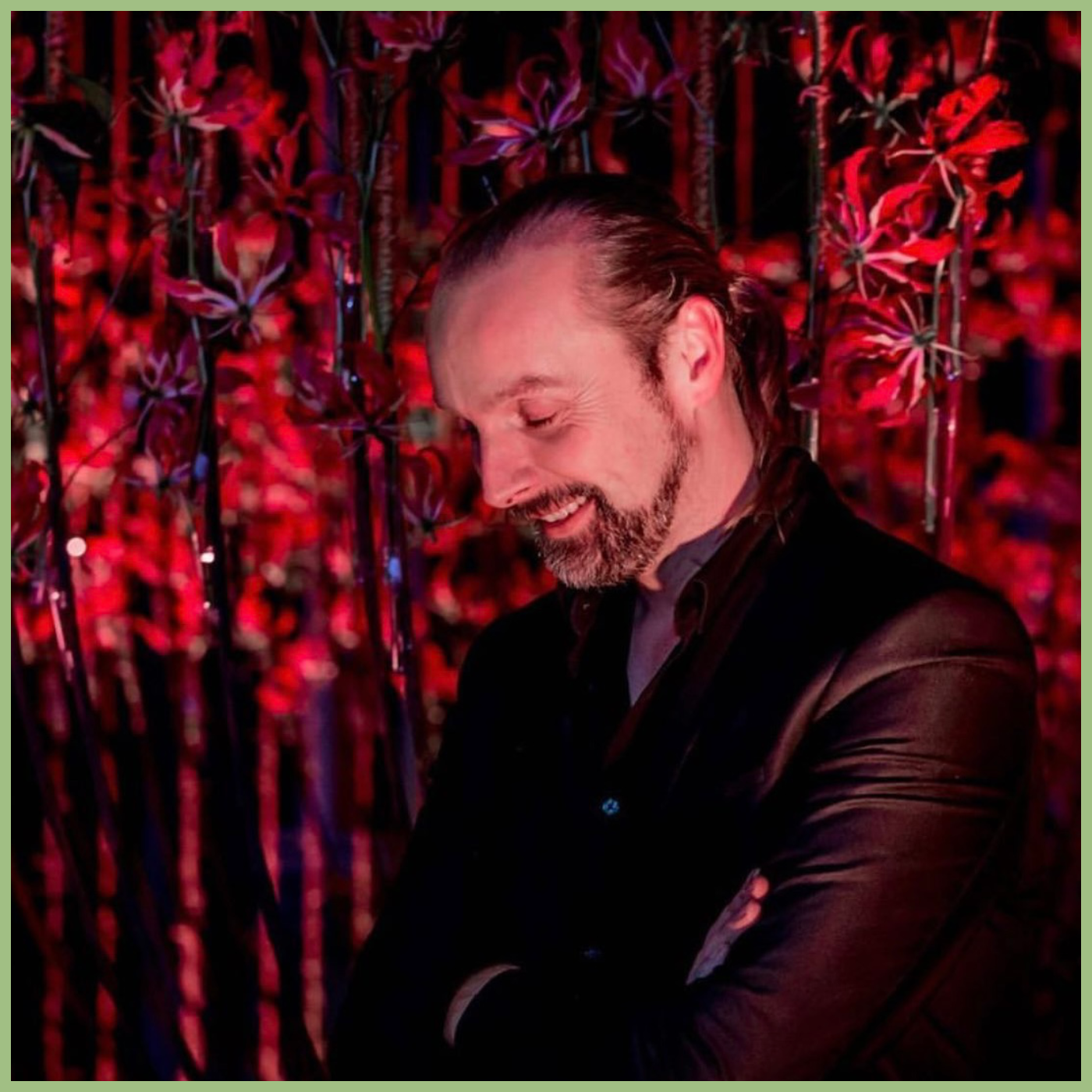 Tom de Houwer florist in Belgium standing in front of red floral wall