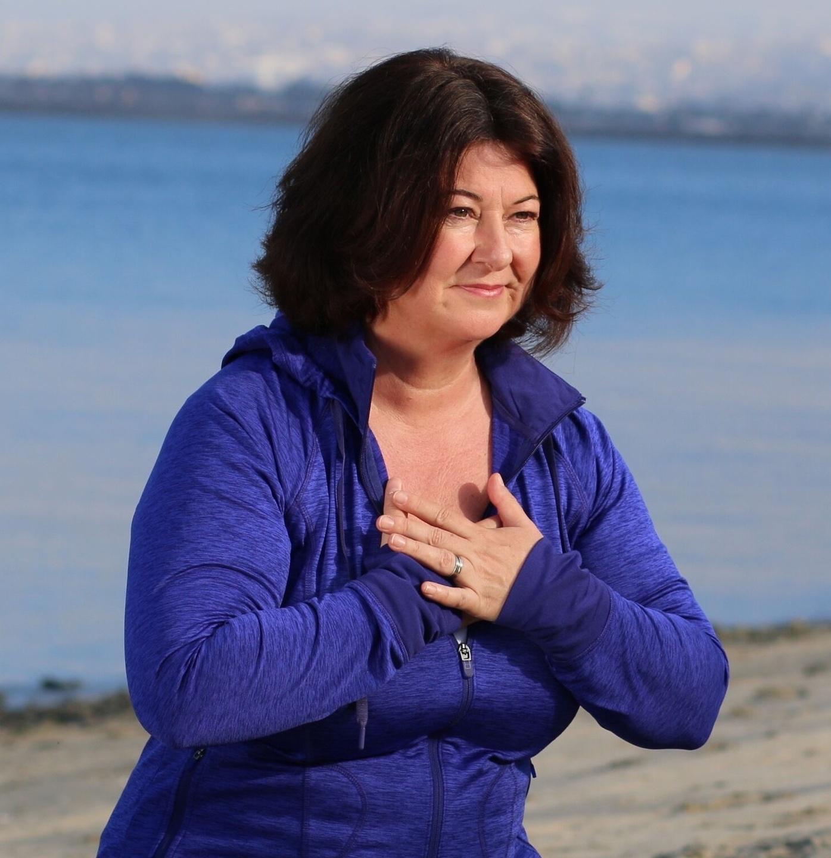Maria Furlano blue jacket on beach hands over heart