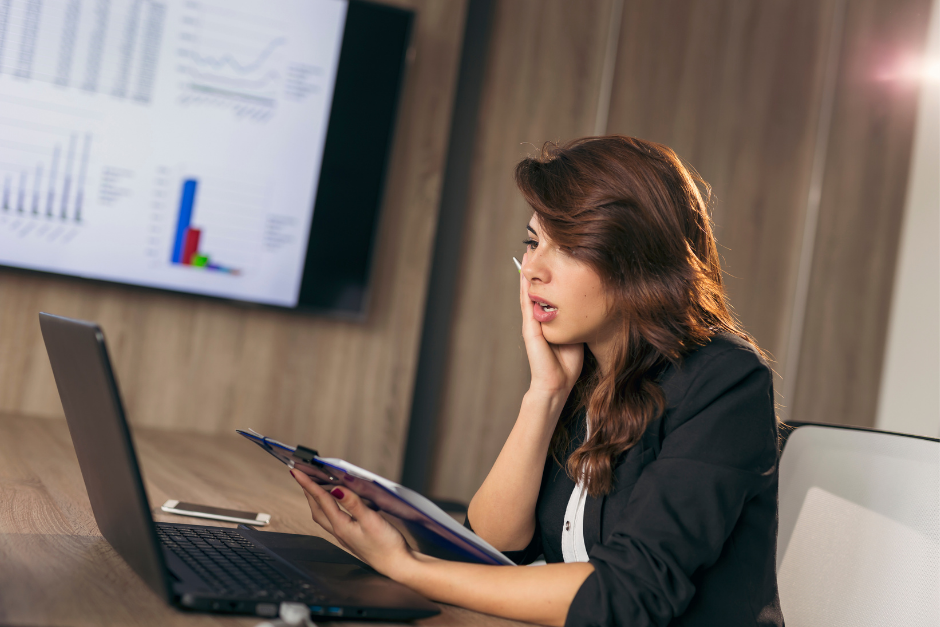 woman at computer looking nervous and anxious holding a clipboard with bookkeeping numbers and charts