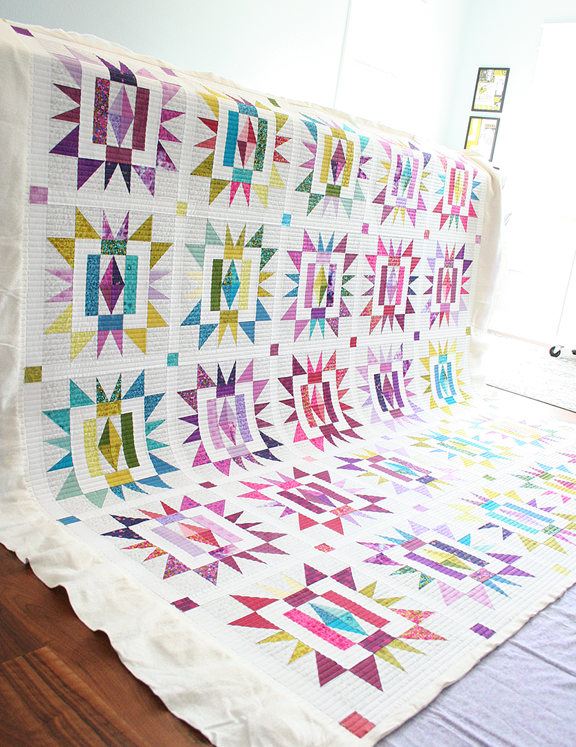 Bright and colorful quilt in rainbow colors with prominent stars and diamond shapes