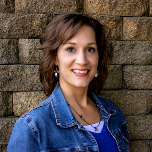woman in jean jacket standing by brick wall