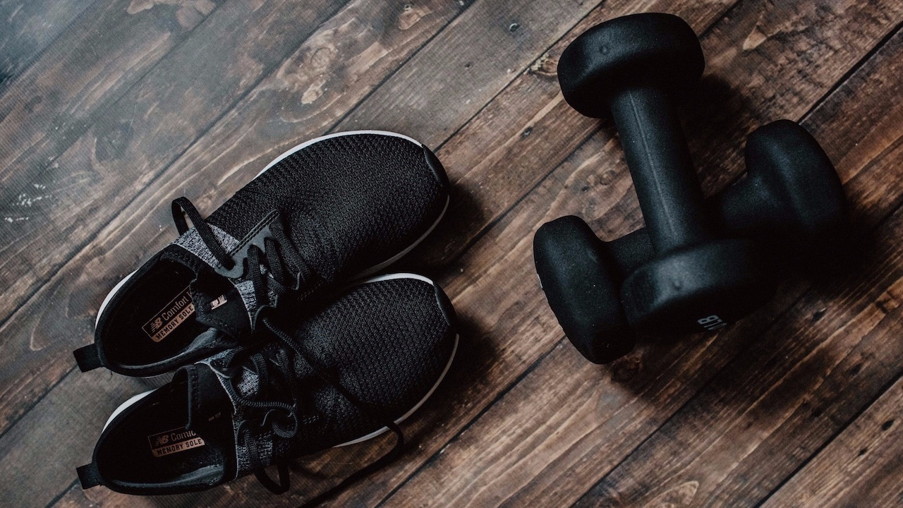 black shoes laying on floor next to hand weights
