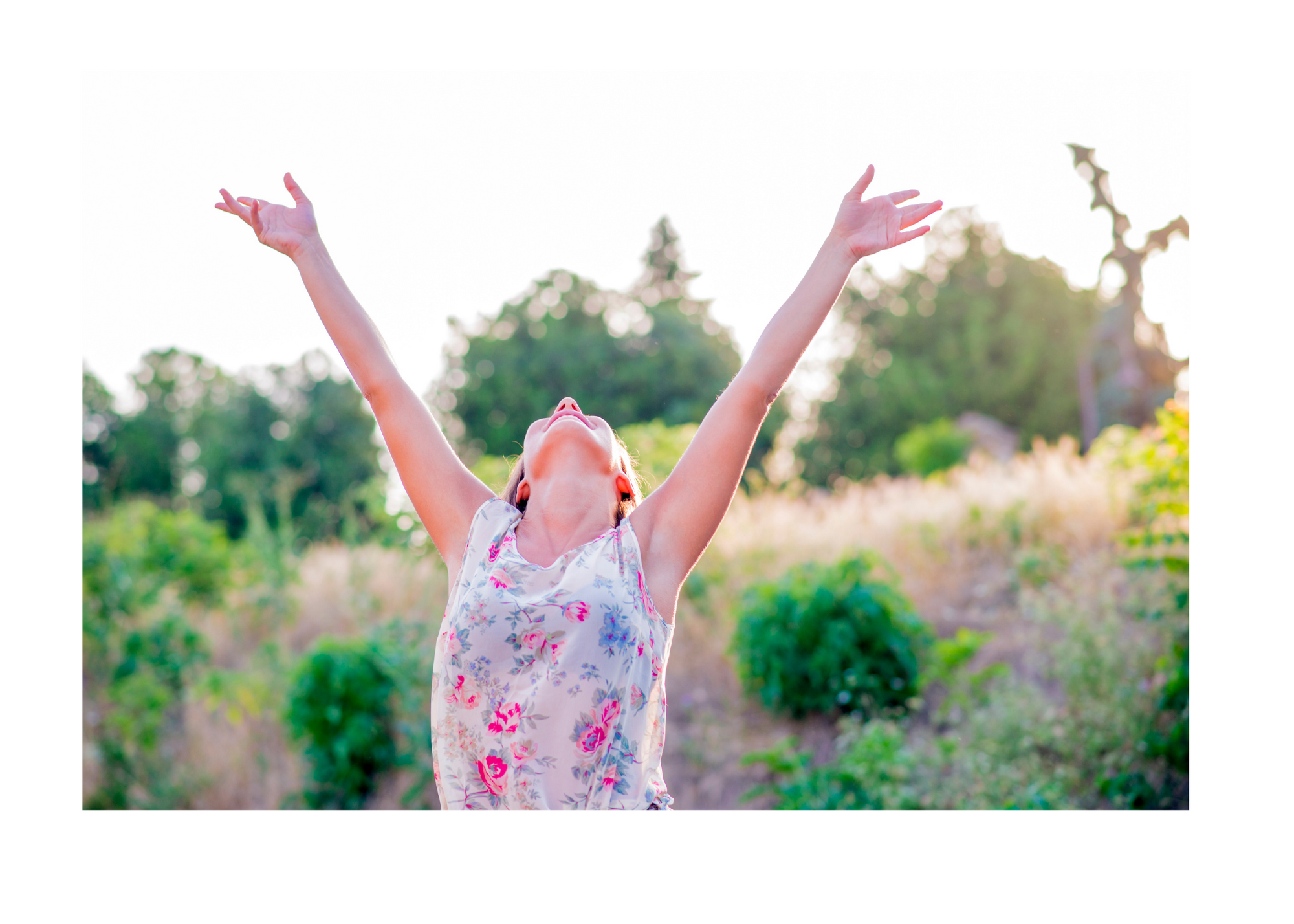 A joyful person in a flowered top raises their arms to the sunshine