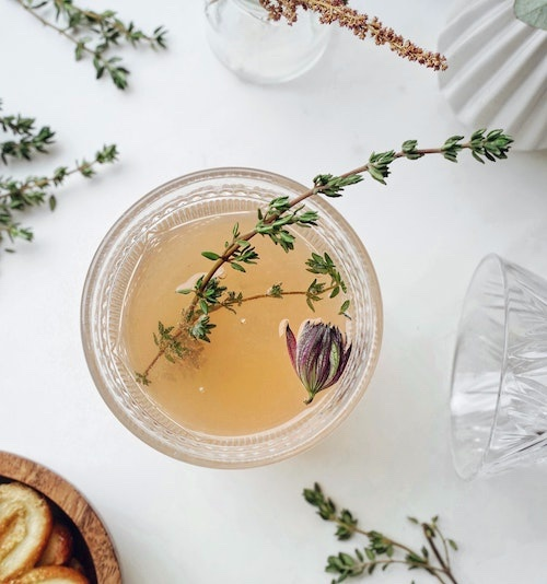 clear glass tea cup with herbs