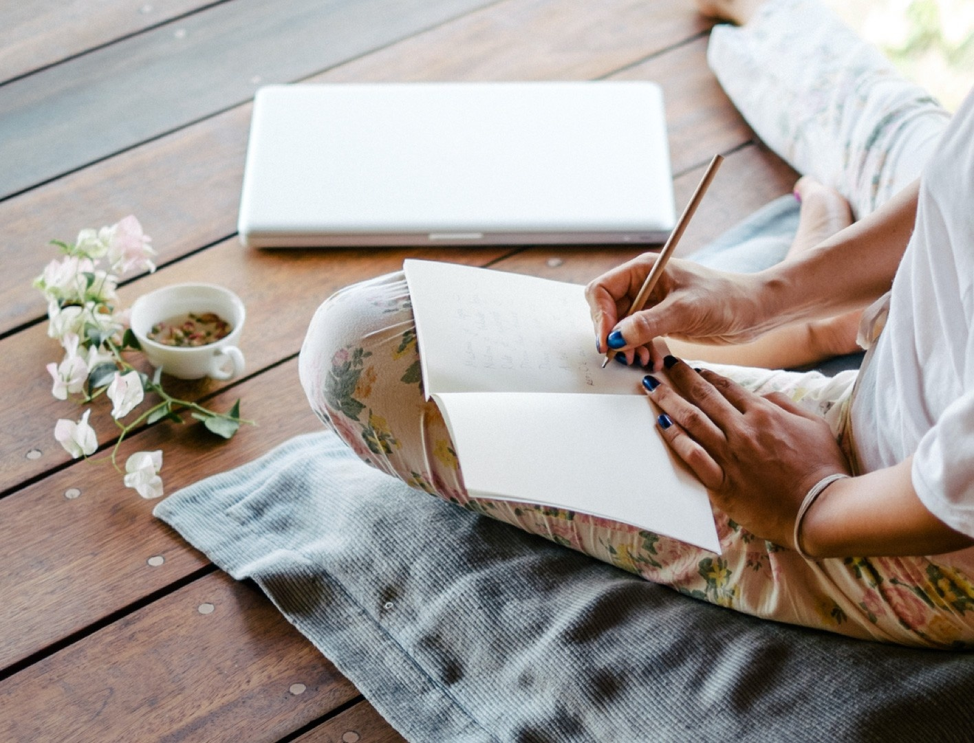 Image of woman writing her journey in a notebook and meditating.