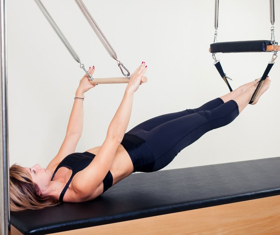 lady on a clinical pilates trapeze table doing bridging exercise in black crop top and leggings