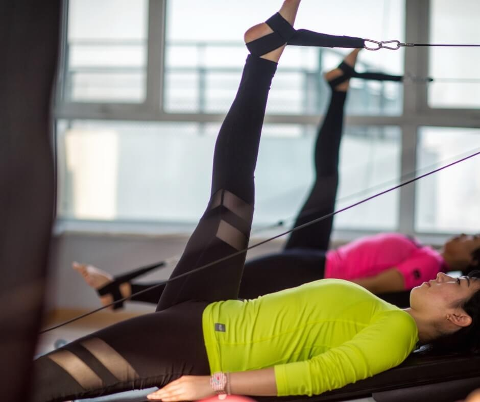 two ladies performing feet in straps exercise on the pilates reformer machine