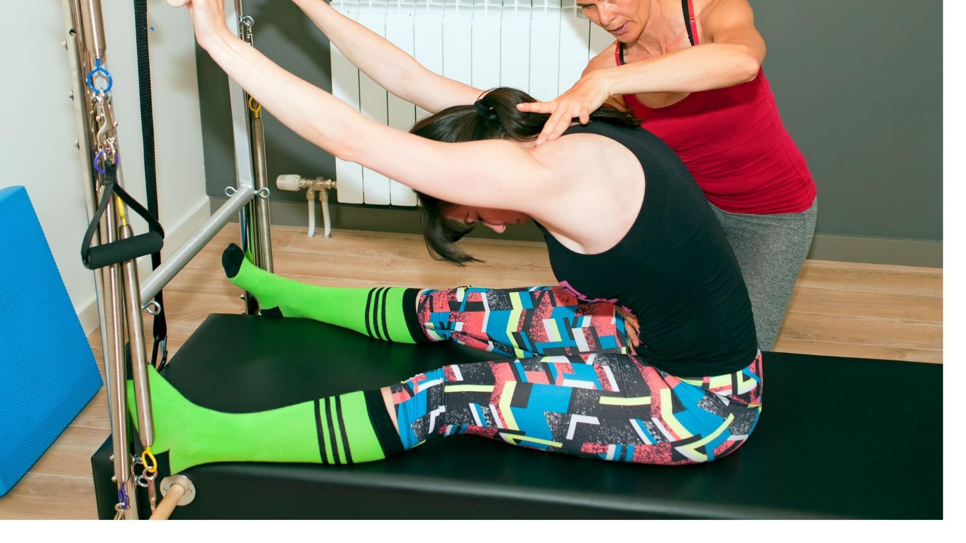 lady doing clinical pilates physio rehabilitation on  pilates trapeze table performing the assisted roll down exercise under guidance from a physio