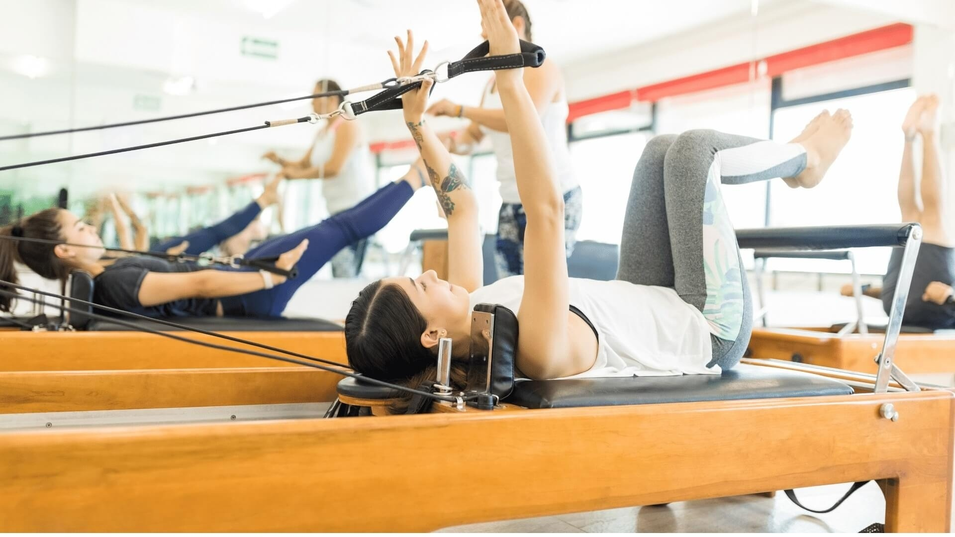 group of adults doing a pilates reformer class being guided by a Pilates Instructor through arms in straps and the pilates hundreds exercise.