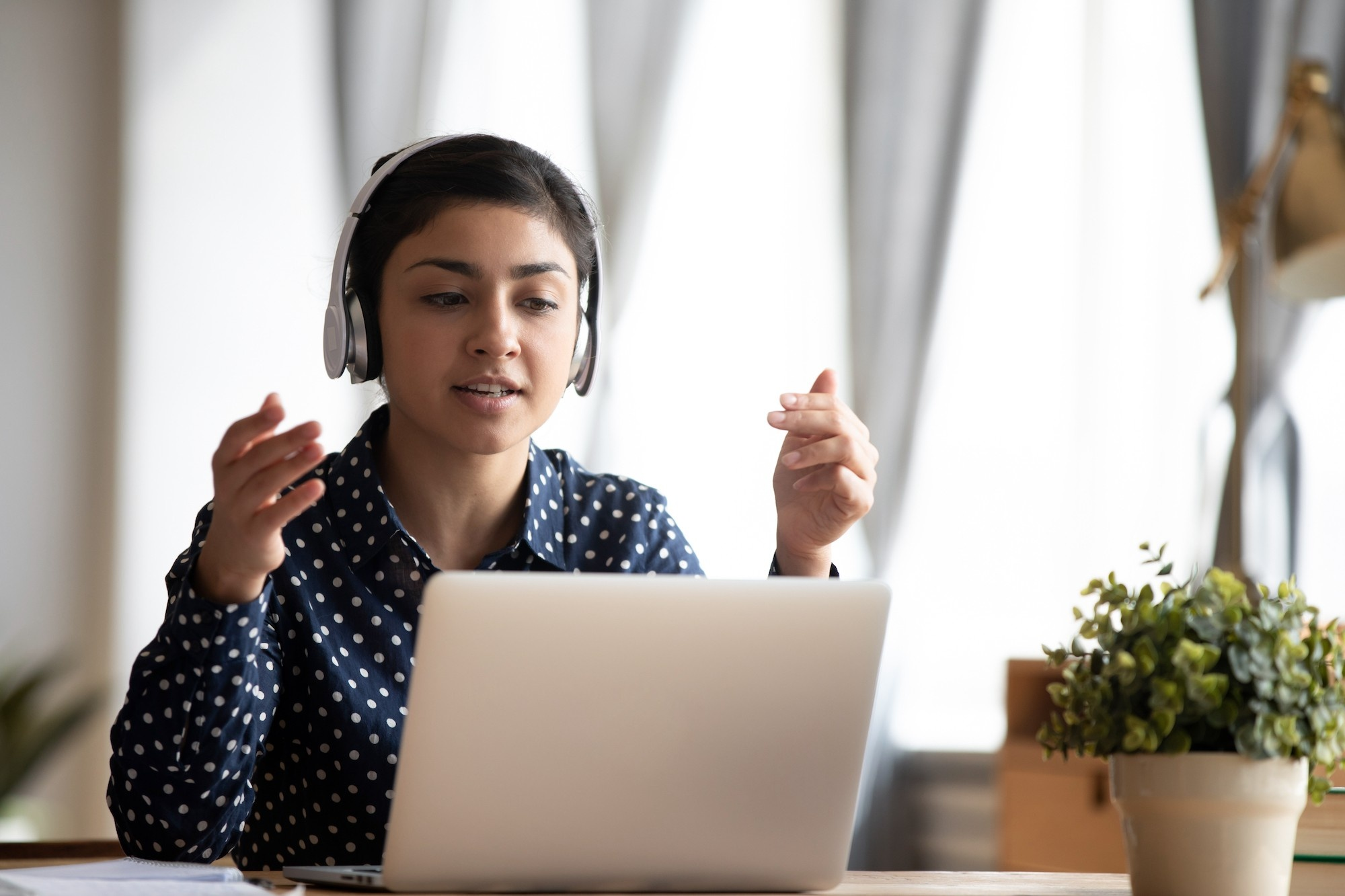 Woman working with headset at laptop