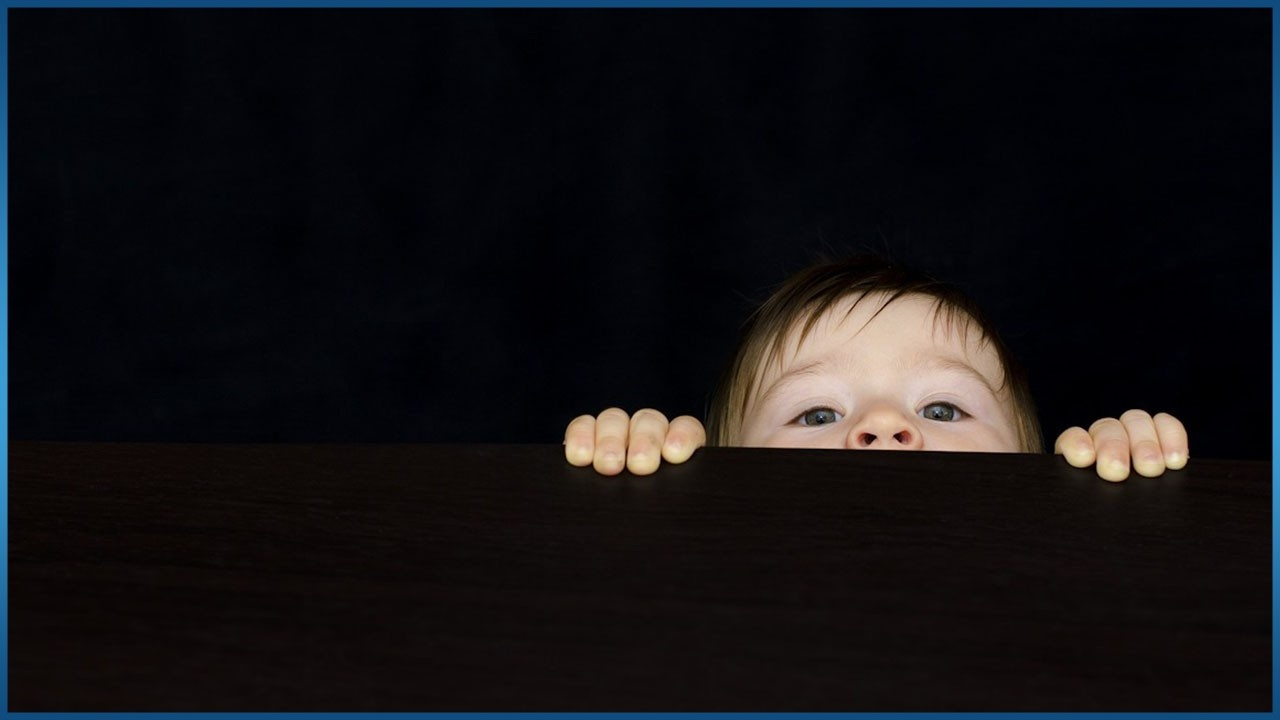 baby straining to see over table