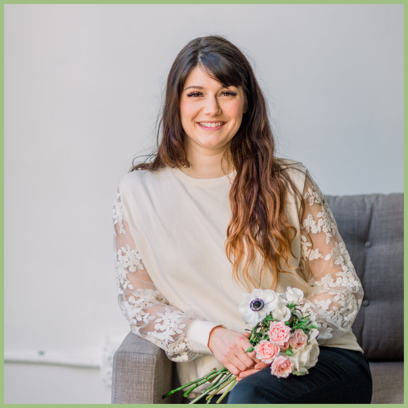 Girl seating on the couch holding bouquet of flowers and smiling Gina Thresher
