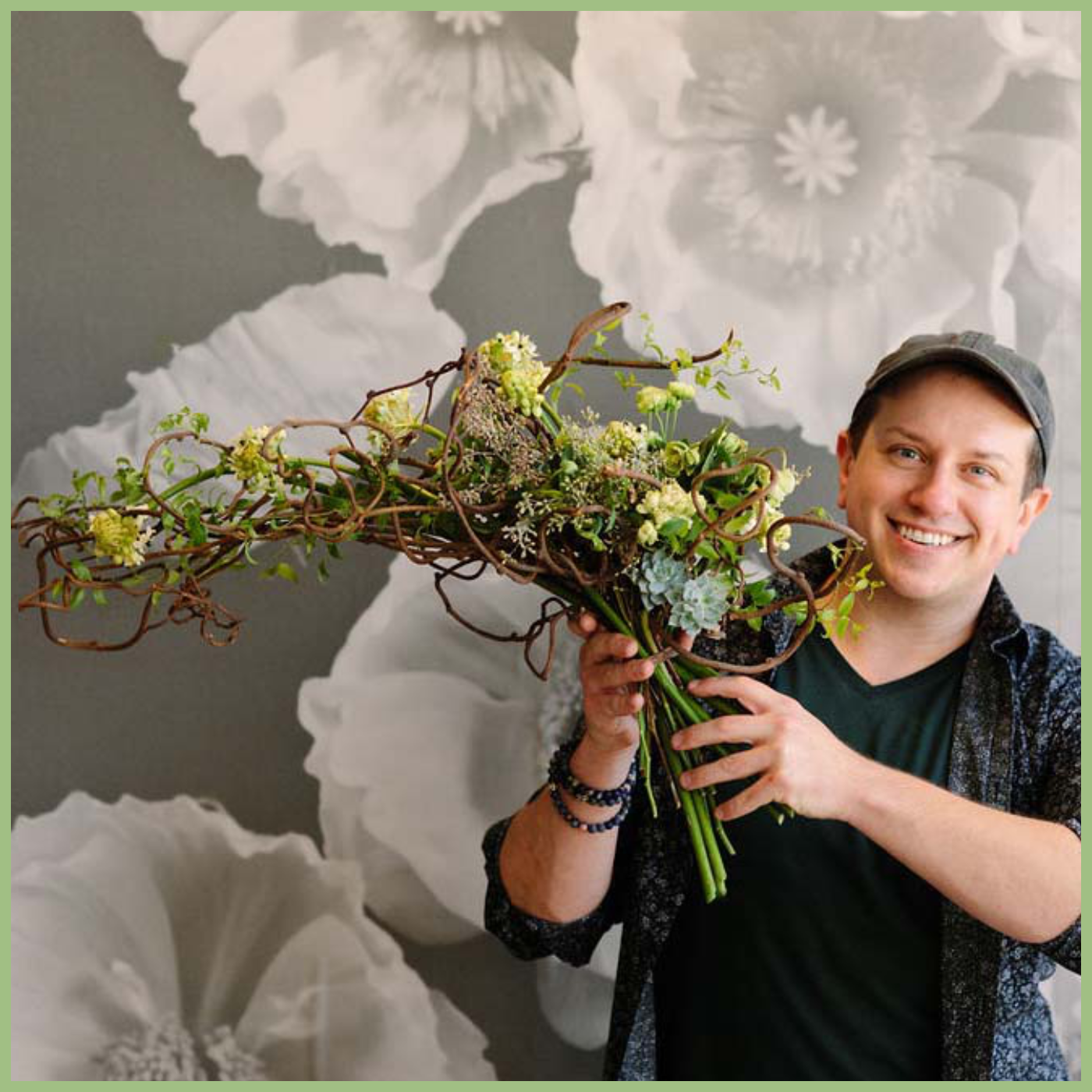 Guy holding a modern bouquet of flowers and smiling Shawn Michael Foley