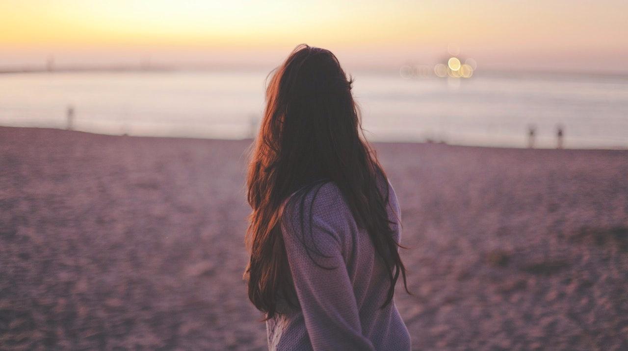 sad woman walking on beach