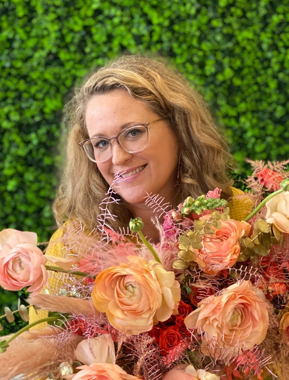 woman smiling holding a bouquet of flowers in orange pink and peach forViva La Flora Live Podcast