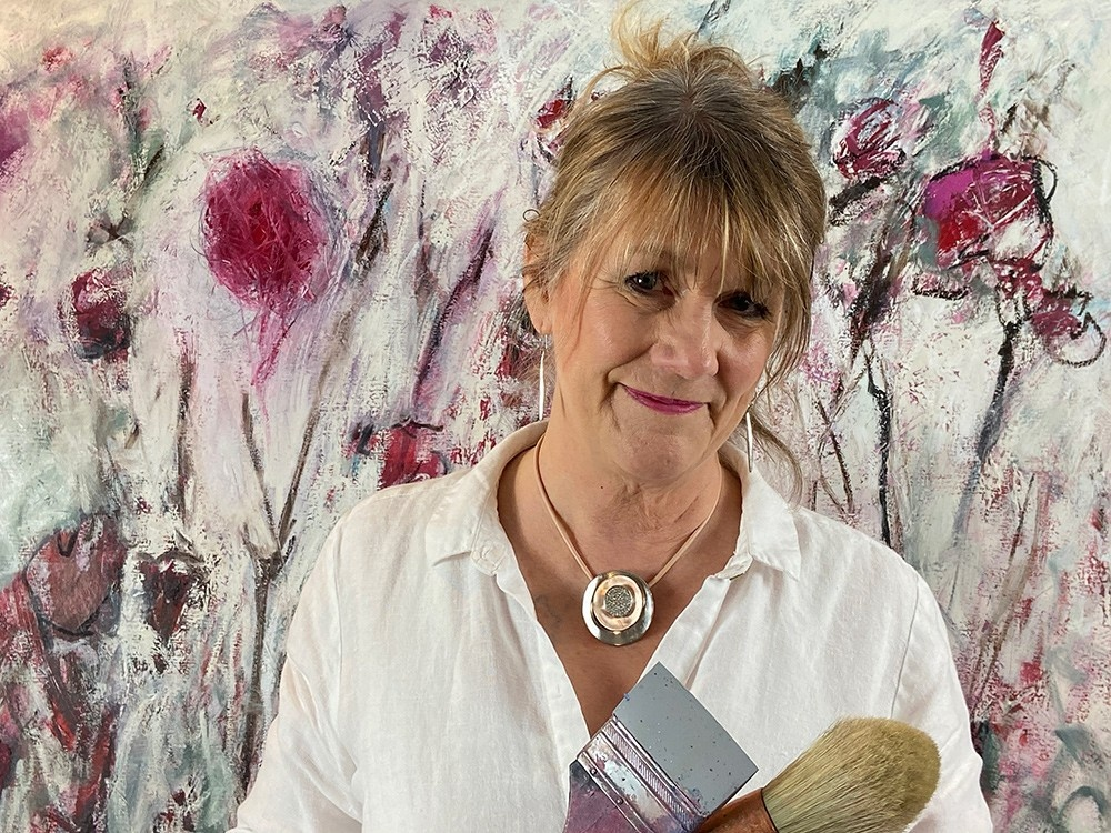 Photo of Dawn Boyer in front of unfinished abstract painting