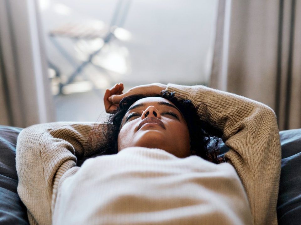 Woman lying on bed with eyes closed