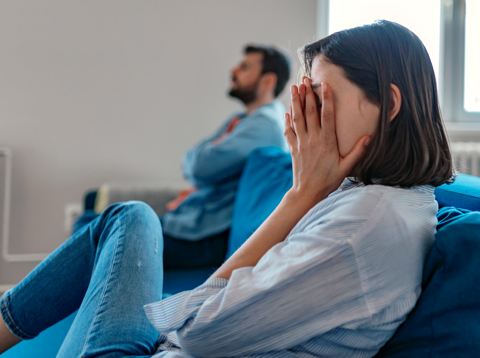 Woman sitting on opposite end of sofa from partner with her face in her hands
