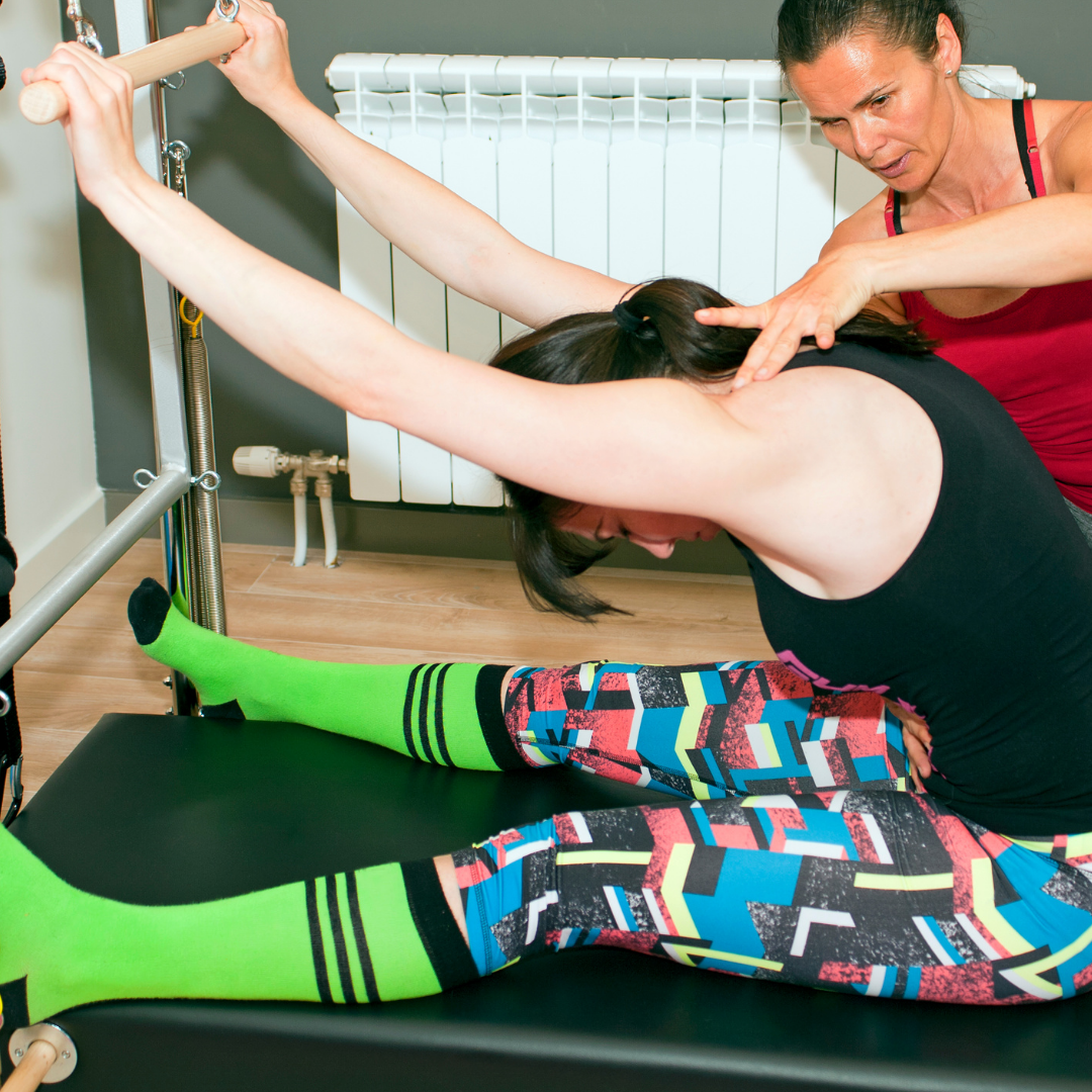 lady on colurful leggings and long green socks working on assited push through on the roll down bar of a pilates trapeze table being guided by her physiotherapist through clinical pilates