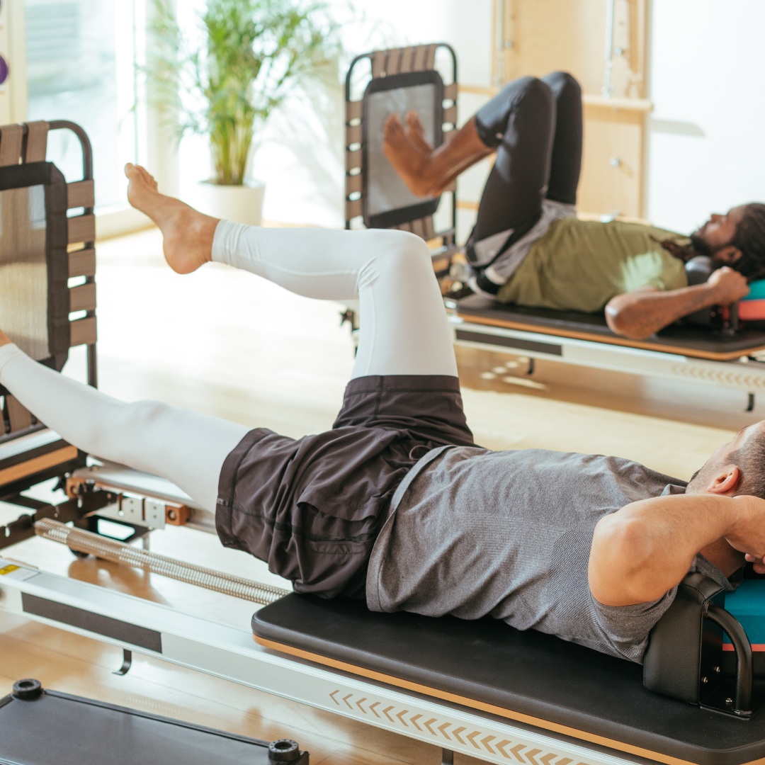 2 men on two pilates reformer machines doing leg work with a jump board for rehabilitation using clinical pilates for back pain