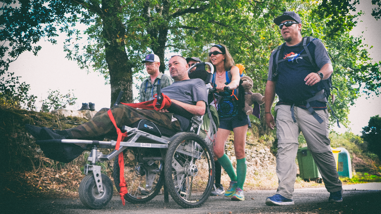 Justin and his wheelchair and group walking on the Camino